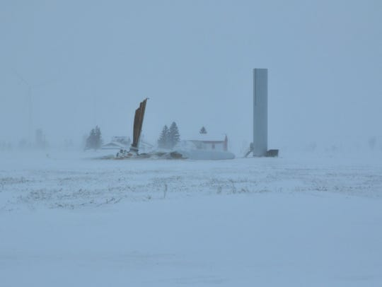 Wind blows snow past a fallen wind turbine on Thursday,
