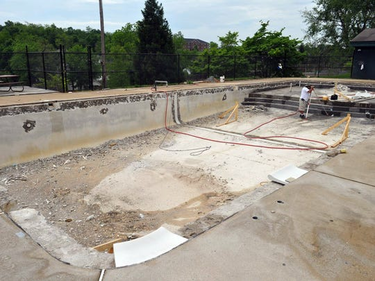 Workers remodel the pool at Montgomery Hall. The debate over the recreation site was settled last year in favor of investing in the pool liner and adding a splash feature and reopening for the community.