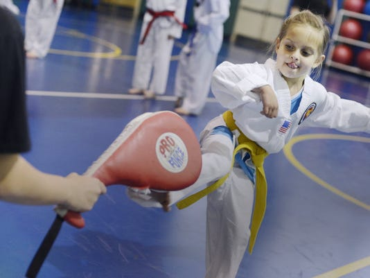 Kathryn Sipe, 6, practices a kick during Tae Kwan Do class in May at the YMCA's Eastern Branch in Hellam Township. Both Kathryn, 9, have Asperger's syndrome, as well as sensory processing disorder. (Daily Record/Sunday News -- Kate Penn)