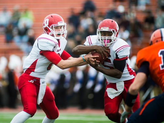 Dickinson's quarterback Billy Burger hands off to Cedric Madden on Saturday at Mussleman Stadium.