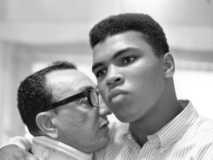 Cassius Clay with boxing manager Chris Dundee around the time of his world heavyweight championship fight against Sonny Liston on Feb. 25, 1964, in Miami Beach, Fla. Clay went on to shock the world, securing his first heavyweight title at the age of 22. He also surprised many the day after, announcing his allegiance to the Nation of Islam and name change to Muhammad Ali.