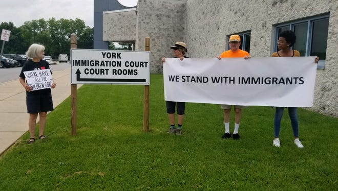 Members from Indivisible York, a local organization that advocates for political reform, hold protest signs in front of York County Prison's federal immigration wing on July 12, 2019.