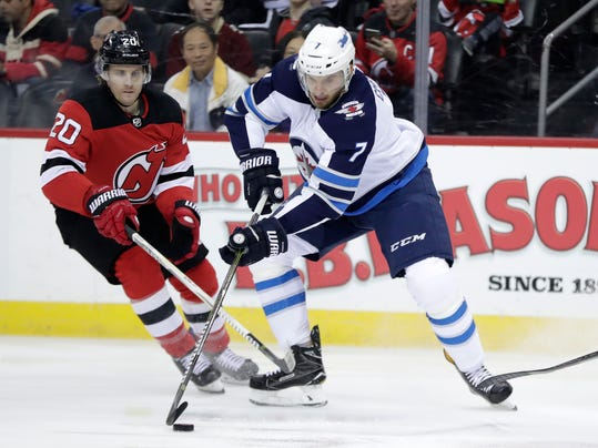 Winnipeg Jets defenseman Ben Chiarot (7) skates with the puck as New Jersey Devils center Blake Coleman (20) defends during the first period of an NHL hockey game, Thursday, March 8, 2018, in Newark, N.J. (AP Photo/Julio Cortez)