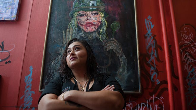 Vanessa Torres stands before a painting in her new shop, One Love, an art gallery and tattoo studio on Landis Avenue in Vineland.