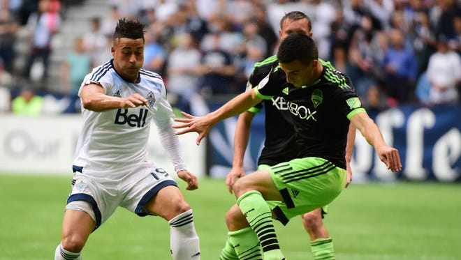 Vancouver Whitecaps forward Erik Hurtado battles for the ball against Seattle Sounders midfielder Aaron Kovar during the first half of the CONCACAF Champions League at BC Place.