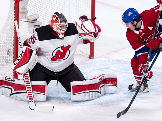 New Jersey Devils goaltender Cory Schneider snags the puck as Montreal Canadiens' Brendan Gallagher looks for a rebound during the first period of an NHL hockey game, Thursday, Dec. 14, 2017 in Montreal.