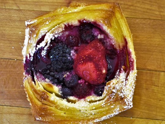 A pastry with mixed berries sits on the counter on