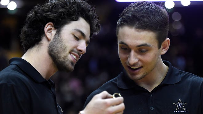 Vanderbilt baseball players Dansby Swanson and Rhett Wiseman check out their College World Series rings, which they received Tuesday during halftime of the men's basketball game against Auburn.