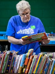 Volunteer Carol Gibson sorts through children's books Wednesday as Henderson's Holy Name school prepares for this weekend's annual book sale. The is the 36th year that Gibson has helped out with the sale that is the main fundraiser for the school's library.