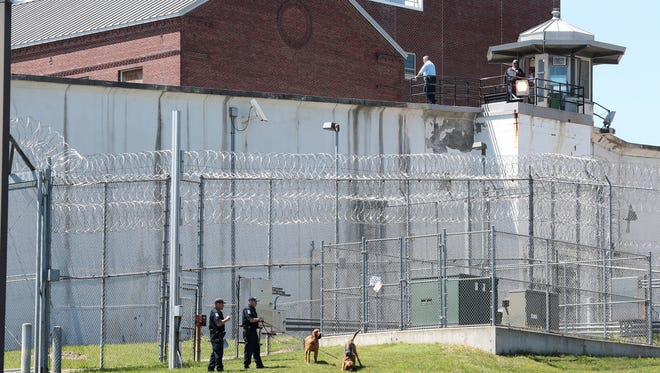 Law enforcement officers with bloodhounds stand guard Saturday at one of the entrances to the Clinton Correctional Facility in Dannemora, N.Y. Two convicted murderers used power tools to cut through steel pipes at the maximum-security prison near the Canadian border and escaped through a manhole, Gov. Andrew Cuomo said Saturday.