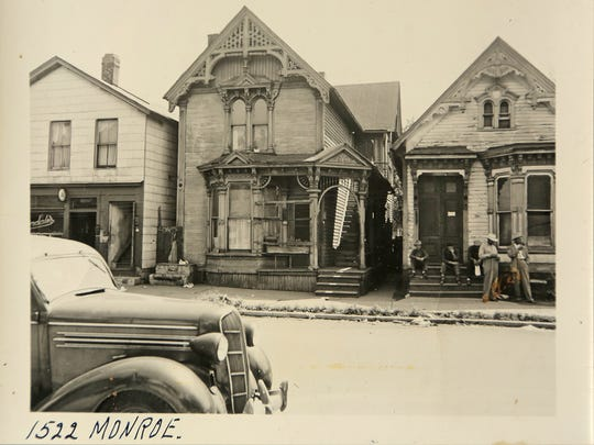 This is a historical photo of Black Bottom before it was torn down in the 1950s to make way for the Chrysler Freeway and the Detroit Medical Center. In this photo five men wait outside of a house located near 1522 Monroe St. on August 31, 1949 in Black Bottom, the ancestral neighborhood of many metro Detroit African Americans.