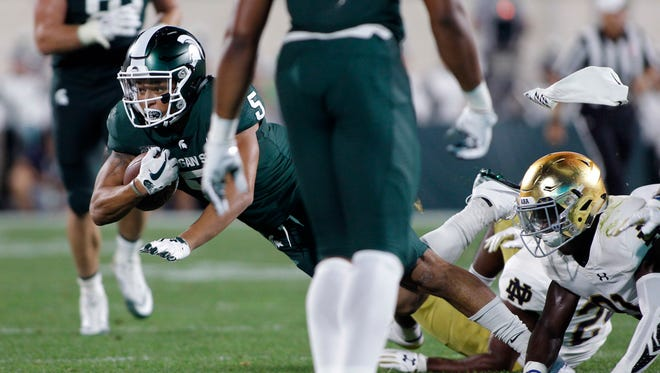 Michigan State receiver Hunter Rison, left, is tripped up by Notre Dame's Jalen Elliott, right, and Nick Coleman, rear, during the second quarter of an NCAA college football game, Saturday, Sept. 23, 2017, in East Lansing, Mich.