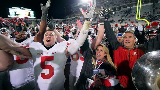 Ohio State tight end Jeff Heuerman (5), coach Urban Meyer and others celebrate after a win at Michigan State on Nov. 9, 2014.