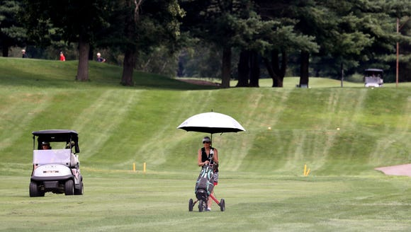 A golfer uses an umbrella as a shield from the sun