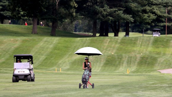 A golfer uses an umbrella as a shield from the sun while playing golf at Maple Moor Golf Course in White Plains July 27, 2018. Despite several days of rain recently, the golf course was dry. Golfers said the course was in great condition.