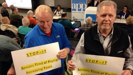 Attendees hold up signs at a session of APP's #TaxedOut Tax Appeal Workshop.
