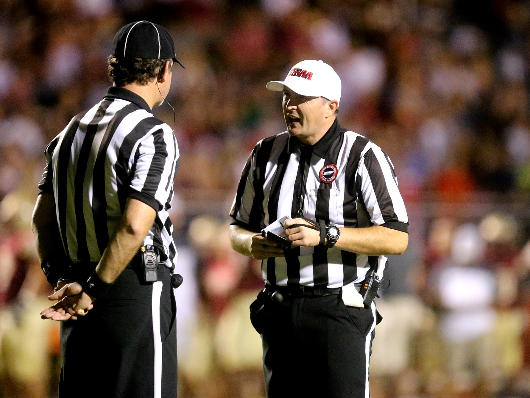 Referees Peter Keating, left and Jeremy Tollison talk during a break in the action of the Riverdale football game against Blackman on Sept. 2, 2016.