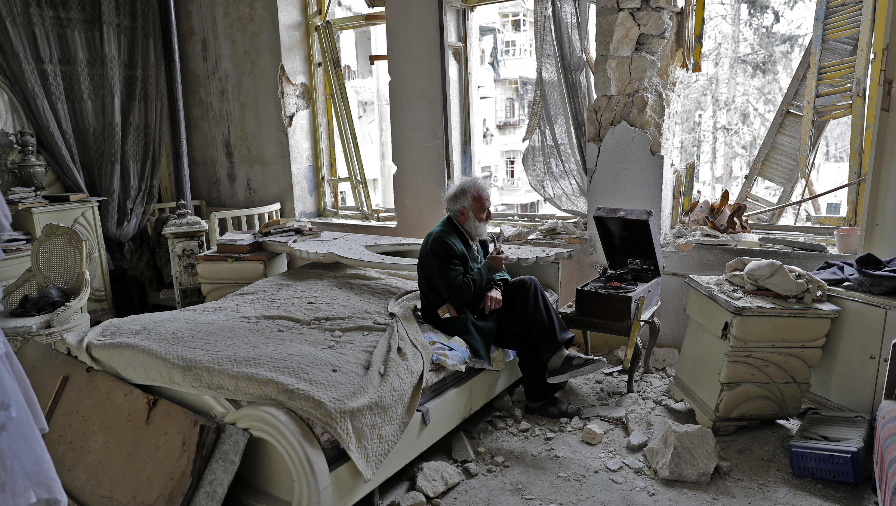 A Man Listening To A Record Player In War Torn Syria And
