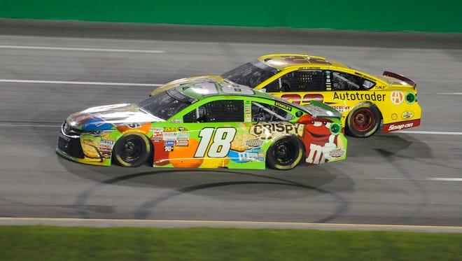 Kyle Busch passes Sprint Cup Series driver Joey Logano for the lead.