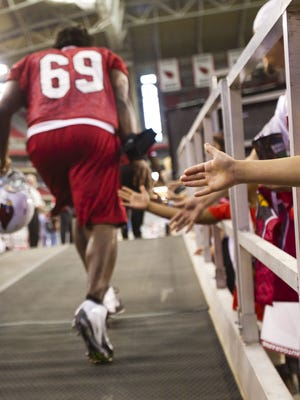 Defensive end Landon Cohen, who's now with Seattle, slaps hands while running out to practice during the Cardinals' first Fan Fest at University of Phoenix Stadium in 2012.