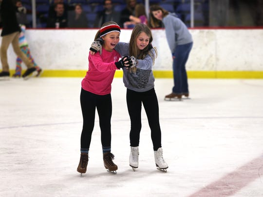 Anna Spellacy, 9, left, and Katelyn Hedrick, 10, both from Indianapolis, try their hand at skate dancing at the Indiana State Fairgrounds' new Youth Arena ice skating rink behind the renovated Coliseum on Friday, Dec. 12, 2014.