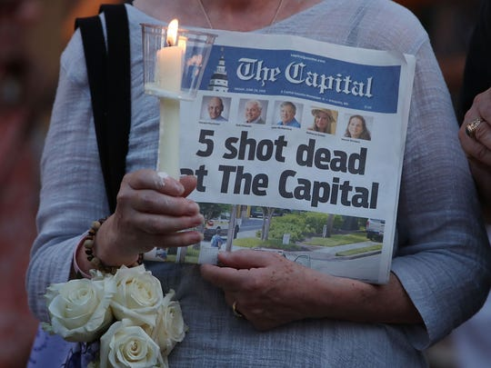 A woman holds the June 29, 2018, edition of the Capital Gazette during a candlelight vigil to honor the five people who were shot and killed the day before in Annapolis, Maryland.