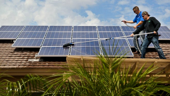 Installers clean solar panels atop a Peoria resident's home in 2010.