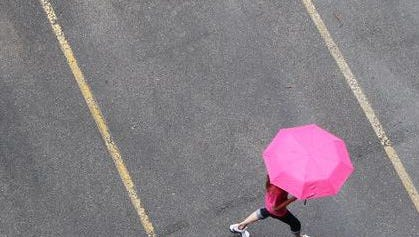 Shielded from the rain by an umbrella, a pedestrian crossed a parking lot in Covington.