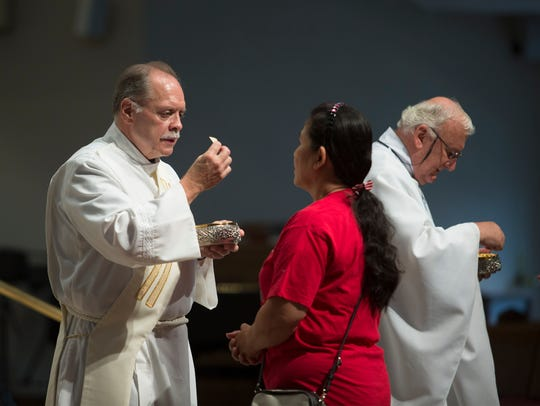 Deacon Frank Weber helps with communion at St. Robert