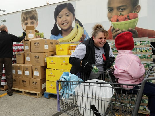 Volunteer Amy Leitzke talks to a child as she puts cans of fruit in the family's cart at a mobile food panty with Feeding America Eastern Wisconsin during this year's kickoff for the USA TODAY NETWORK-Wisconsin's annual Stock the Shelves Campaign outside Lambeau Field in Green Bay.