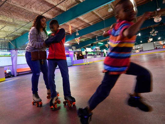 William Gaskins, 10 of York Township, grabs on to his mom Oleonta Stanfield as her grandson, Jaice Stanfield, 4, right, runs past at Roll 'R' Way roller skating rink in York.