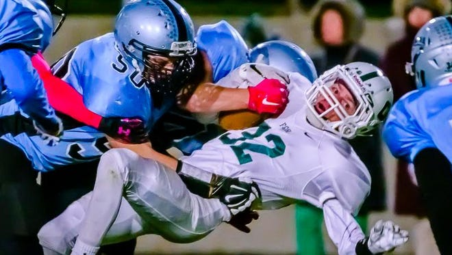 Jake McQueen ,32, of Gabriel Richard is knocked off his feet by Caolan Keenan ,50, of Lansing Catholic and a teammate during their game Friday October 16, 2015 in Holt.