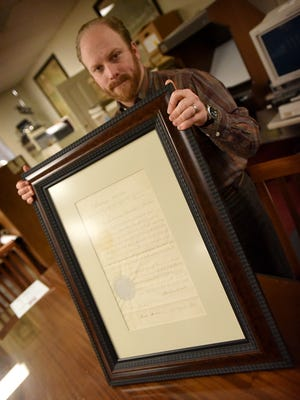Lebanon County Historical Society archivist and librarian Adam Bentz holds the framed letter from Lincoln to Industrialist George Dawson Coleman.