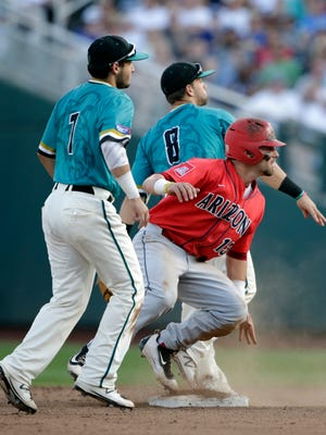 Coastal Carolina shortstop Michael Paez (1), second baseman Tyler Chadwick (8) and Arizona's Cody Ramer (13) look to first after Ramer was forced at second on a double play attempt in the fifth inning in Game 1 of the NCAA Men's College World Series finals baseball game in Omaha, Neb., Monday, June 27, 2016. Arizona's Zach Gibbons was safe at first on the fielders choice. (AP Photo/Nati Harnik)