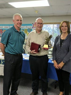NSSD Superintendent Andy Gardner (left) and board member Laura Wipper (right) present Dave Kinney with an NSSD Golden Eagle Award.