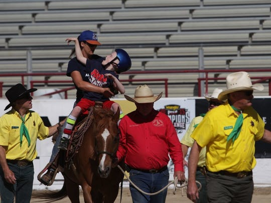 Andreas Fuhrmann/Record SearchlightKacey Tweedy, a fourth-grader at North Cottonwood Elementary School, rides a horse with his aide, Tiffany Collver, Tuesday, during the Asphalt Cowboys' Special Kids Day at the Redding Rodeo Grounds.