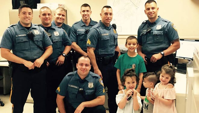 Roxbury Police officers pose with children who stopped by the department to show their support. 7/12/16