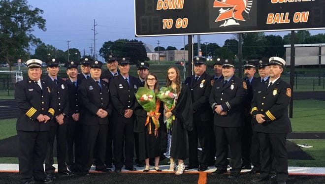 Members of the York City Fire Department's 'B' platoon escorted fallen firefighter Ivan Flanscha's step-daughter, Maya Lehman (middle left), and daughter, Savannah Flanscha (middle right), to York Suburban's graduation on Thursday, May 24, 2018.