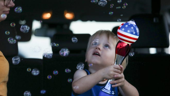Brittani Scott watches her son, Cooper Scott, 2, play with bubbles while waiting to see a display of fireworks Friday in Sarasota, Florida.