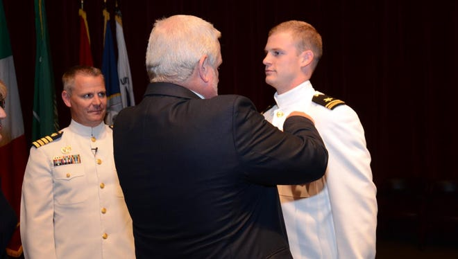 Lt. j.g. Payden Roberts, right, is pinned with his Wings of Gold by his father, Joel Roberts Jr., at a Winging Ceremony presided over by Capt. Kent Everingham, commanding officer of U.S. Coast Guard Station San Francisco, at Whiting Field Naval Air Station on April 27, 2018.