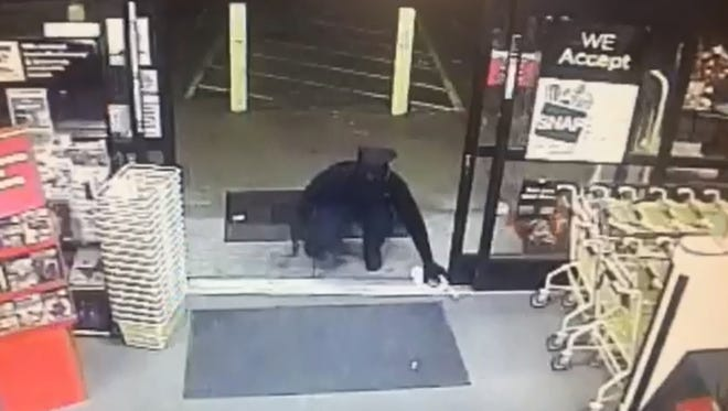 A masked robber is seen on video surveillance entering the store carrying a firearm and rock in this Montgomery County robbery. He uses the rock to keep the automatic doors open while demanding money from the cashier.