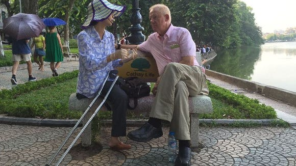 Former POW Charlie Plumb talks to a Vietnamese woman who said her leg was blown off during the bombing of Hanoi in December 1972.