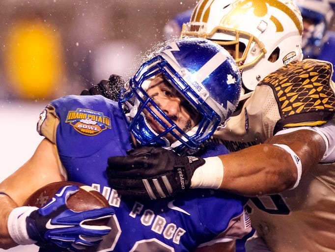 Air Force running back Paco Solano (22) is tackled
