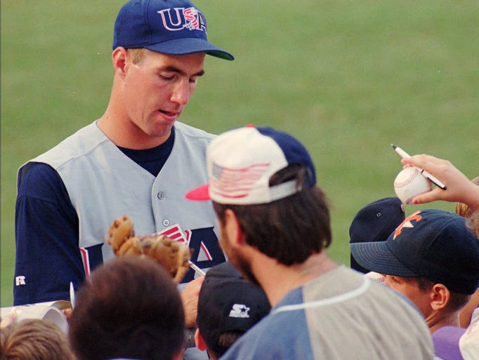 R.A. Dickey, with Team USA, signs autographs before