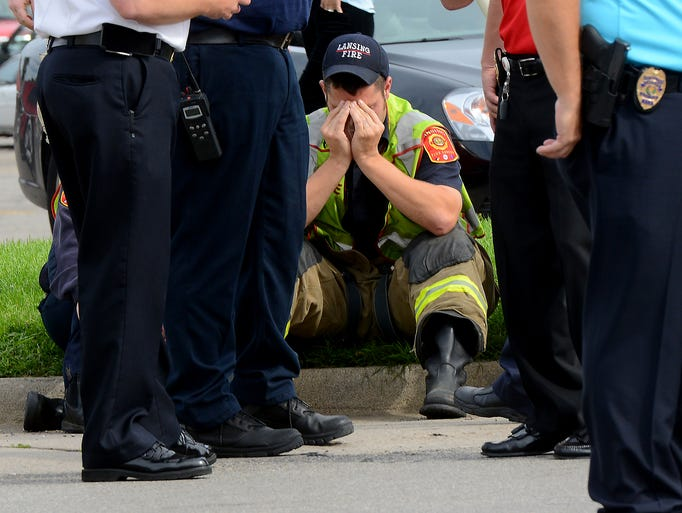 A Lansing firefighter puts his head in his hands while