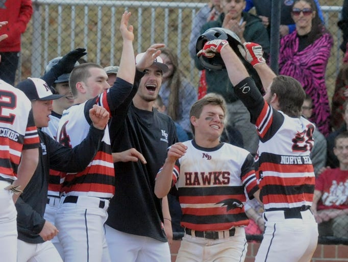 North Buncombe's Dylan Fox  (far right) is greeted by teammates after a home run against visiting Reynolds  Friday. John Coutlakis 3-14-14