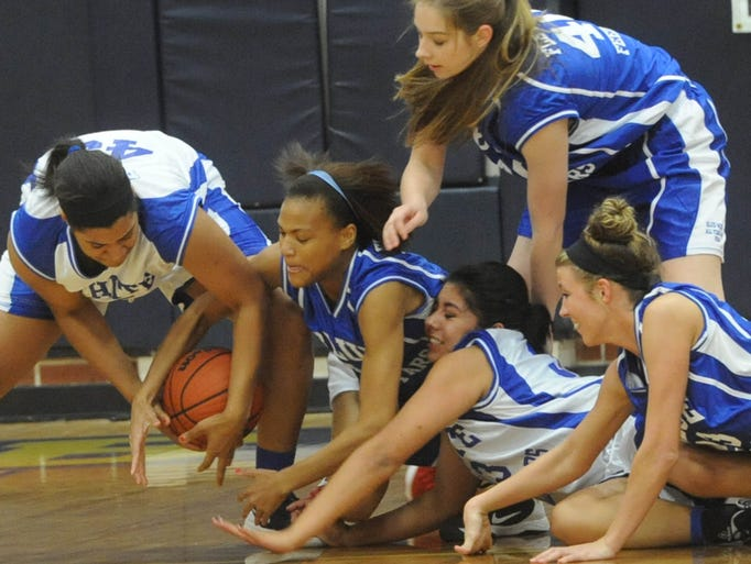 Blue and White girls sprawl for a loose ball during the annual Blue-White All Star game at Roberson Friday. john Coutlakis 3-21-14