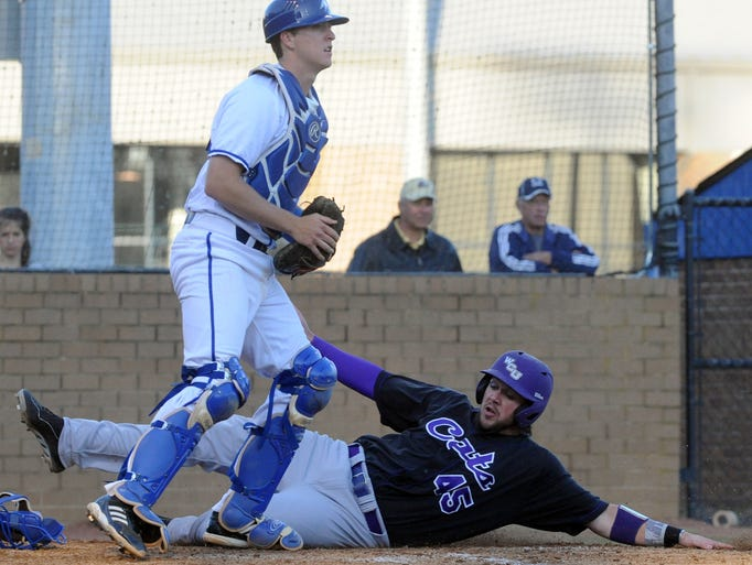 Western Carolina's Taylor Sandefur slides by UNC Asheville catcher Sam Turner to give the visiting Catamounts a 3-0 4th inning lead Wednesday. John Coutlakis 4-8-14