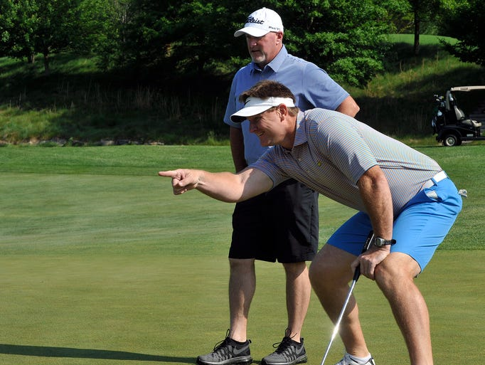 Super Bowl Champion Brad Johnson, front, and former Braves pitcher Darren Holmes look over a putt during the Brad Johnson Celebrity Golf Classic at Walnut Cove Tuesday. 5/21/14. Robert Bradley (rbradley@citizen-times.com)