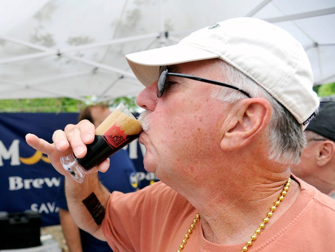Barry Bosinger, from Smith Mountain Lake, Virginia samples a brew from Moon River Brewing at the Beer City Festival at Pack Square Park Saturday. Beer drinkers sampled brews from 30 breweries from across the country. 5/31/14. Robert Bradley (rbradley@citizen-times.com)